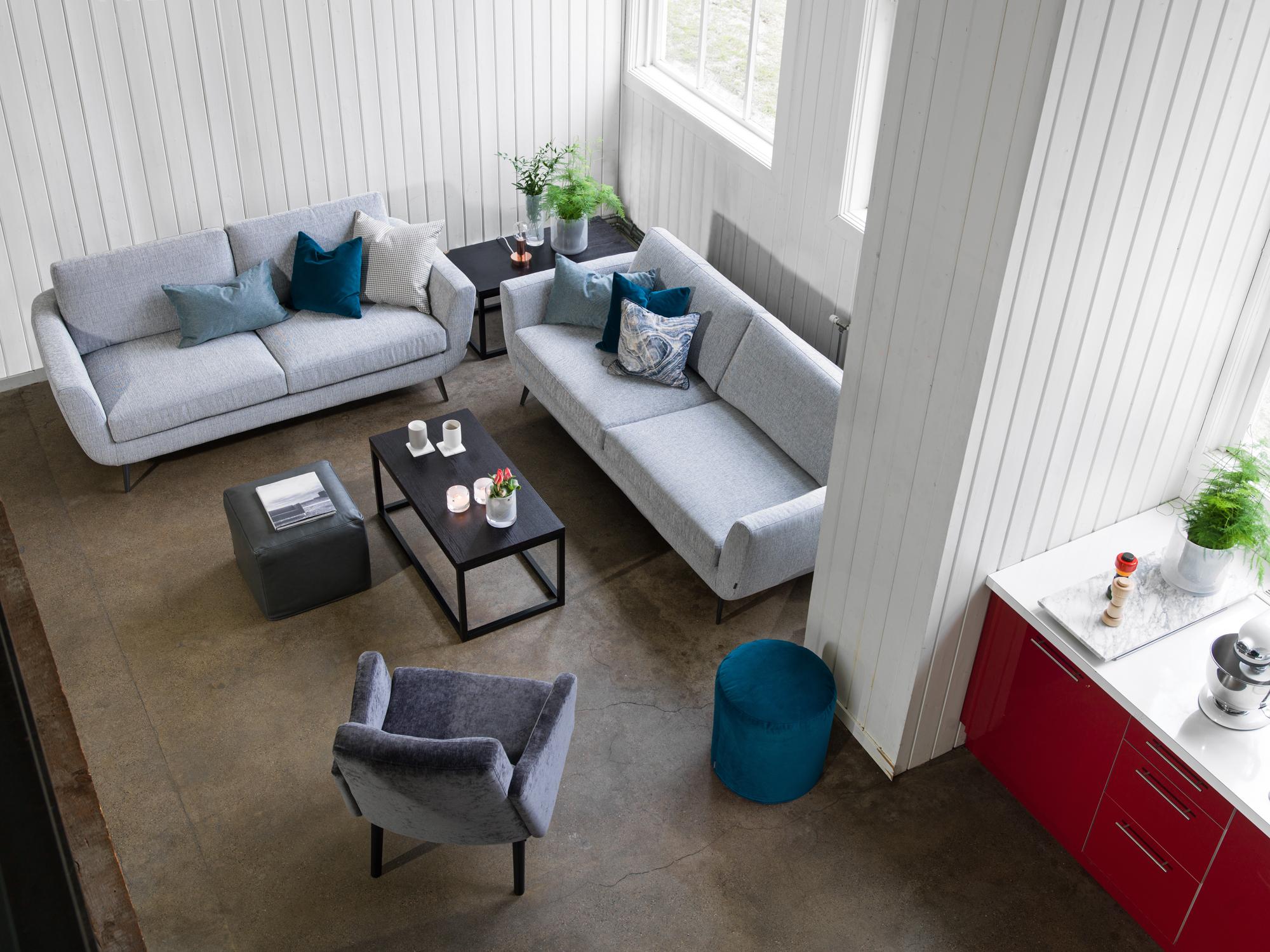Harmaasävyisen olohuoneen sohvakalusteissa on aavistus retrohenkisyyttä  Etu