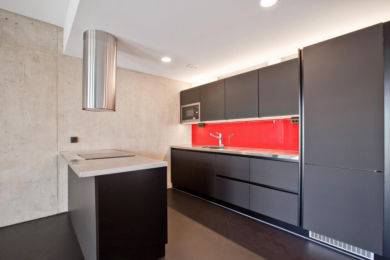 Mustaa, punaista ja betonia loft kodin keittiössä  Etuovi