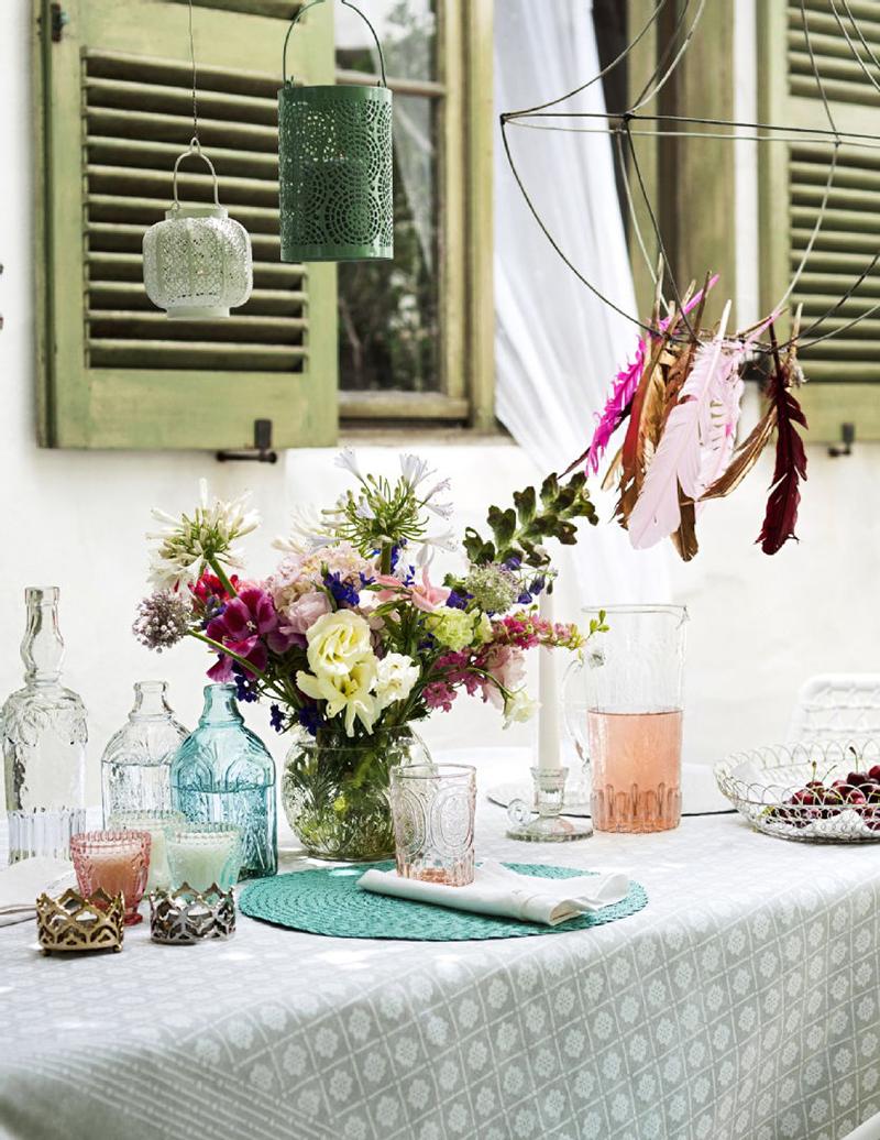 Ruokailutilan kattaus, kesä, astiat, Ideapark: H&M Home tuoksukynttilä, puuvillainen pöytäliina, juomalasi ja metallilankakori