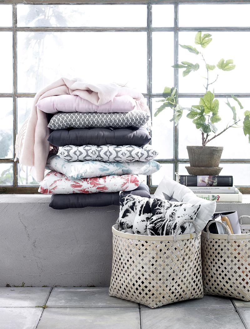 Istuintyynyjä ja muita tekstiilejä terassilla.