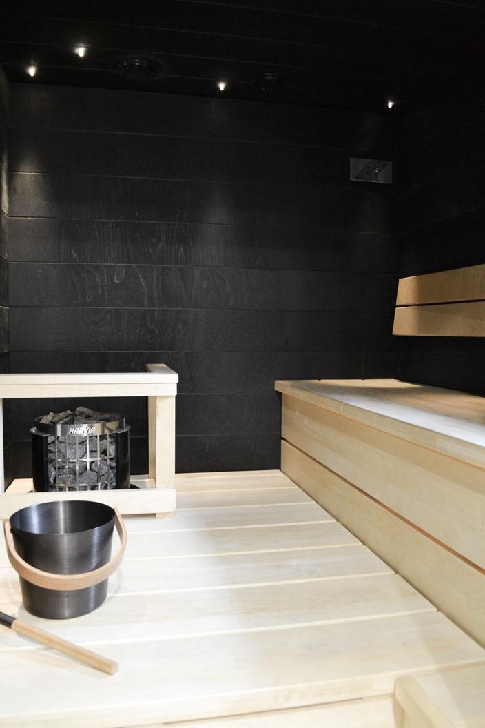 Saunassa mustat seinät ja vaaleat haapalauteet